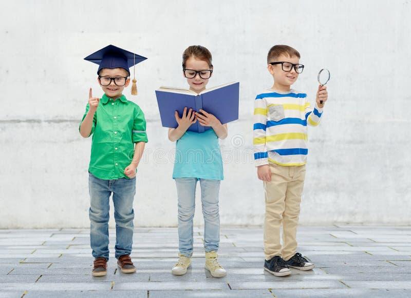 Niños en vidrios con el sombrero del libro, de la lente y del soltero fotografía de archivo libre de regalías