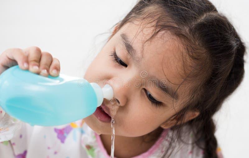 Niños enfermos de la muchacha asiática joven que limpian la nariz con la irrigación nasal fotos de archivo