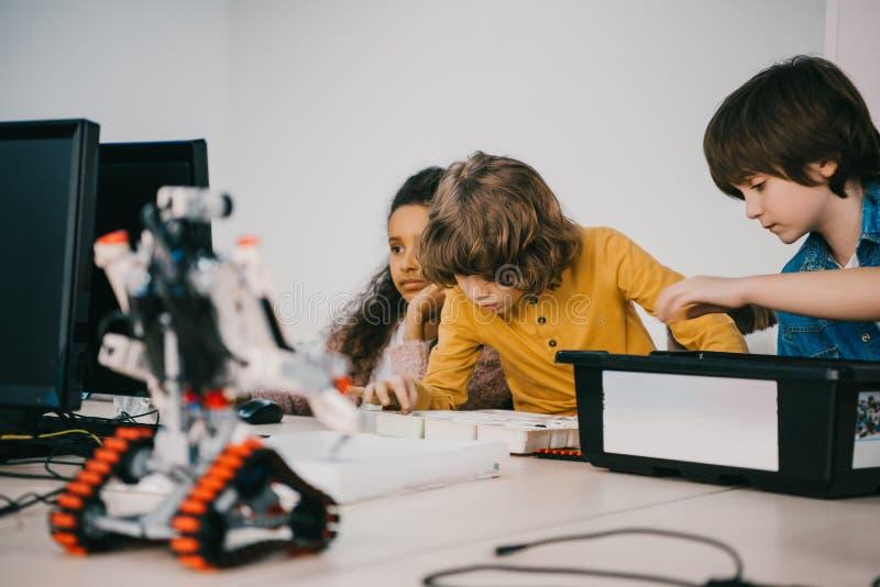 niños enfocados que construyen los robots diy, tronco foto de archivo libre de regalías