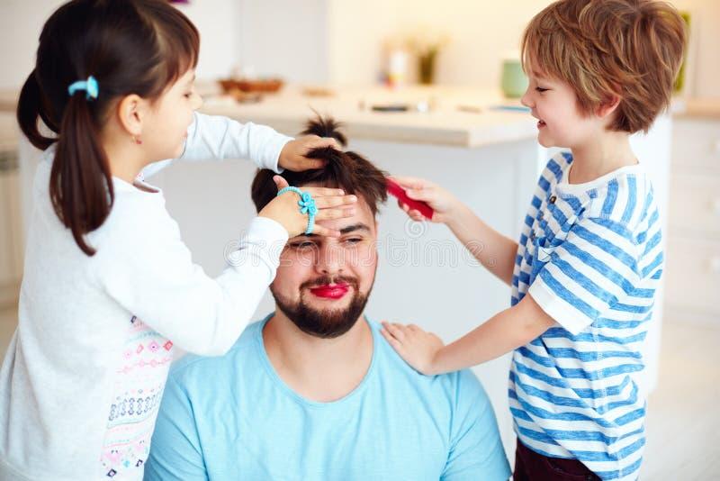 Niños enojados que hacen el peinado y el maquillaje locos al papá en casa fotos de archivo