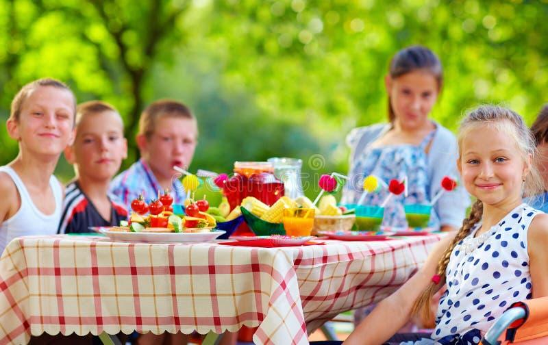 Niños felices alrededor de la mesa de picnic fotografía de archivo