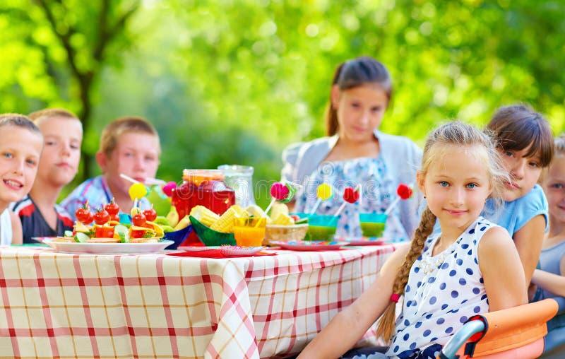 Niños felices alrededor de la mesa de picnic fotos de archivo libres de regalías