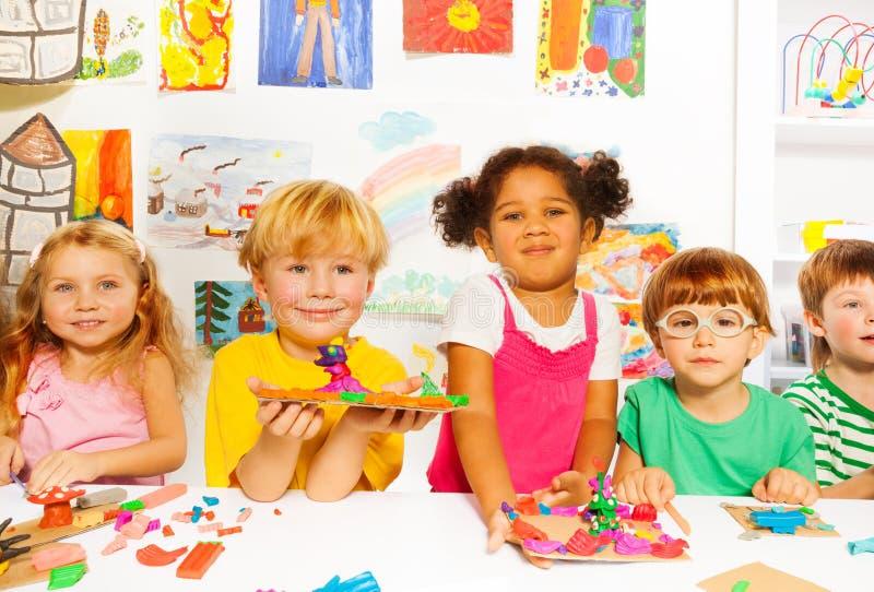 Niños felices con la arcilla de modelado en sala de clase imágenes de archivo libres de regalías