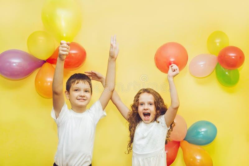 Niños felices con los globos en la fiesta de cumpleaños imagenes de archivo