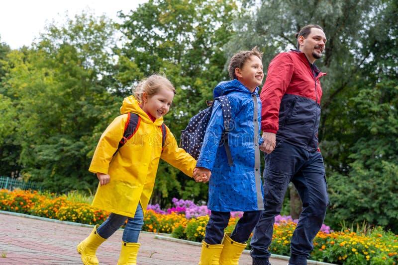 Niños felices con risa de la alegría de ir a enseñar, vestido en impermeables, con una cartera detrás de la mochila fotografía de archivo