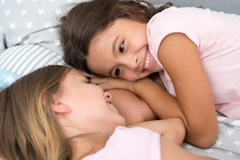 Niños felices día feliz de los niños con dos niñas niñas que sonríen en cama Concepto de familia foto de archivo libre de regalías