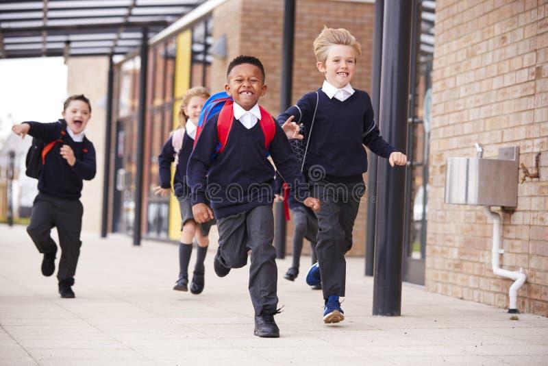 Niños felices de la escuela primaria, uniformes escolares que llevan y mochilas, corriendo en una calzada fuera de su construcció fotos de archivo libres de regalías