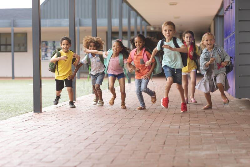 Niños felices de la escuela que corren en pasillo imagen de archivo