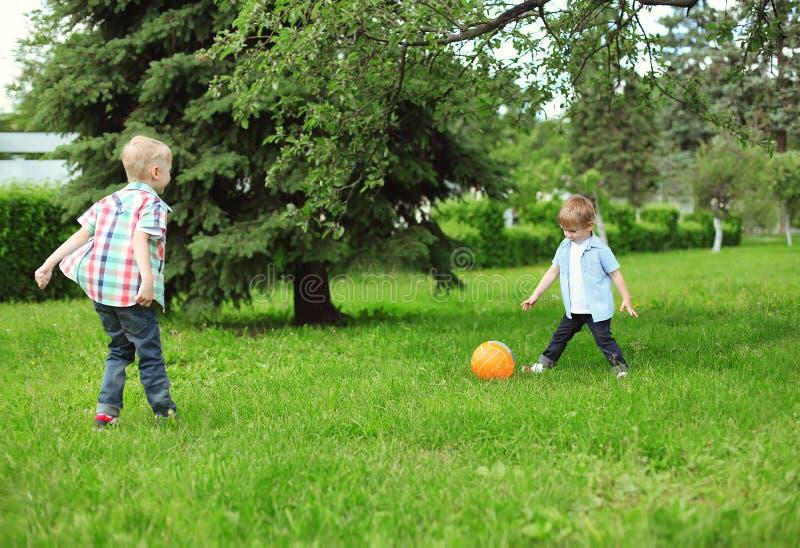 Niños felices dos muchachos junto que juegan al fútbol con la bola imagenes de archivo