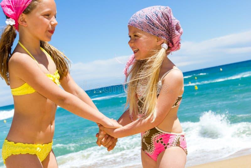 Niños felices en desgaste de la nadada en la playa. foto de archivo