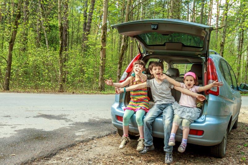 niños felices en el coche, viaje de la familia, viaje de las vacaciones de verano imagenes de archivo