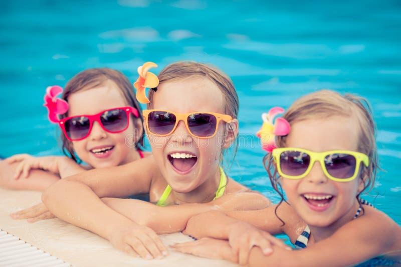 Niños felices en la piscina imagen de archivo libre de regalías