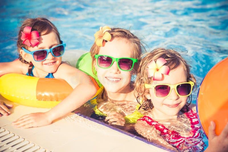 Niños felices en la piscina imagenes de archivo