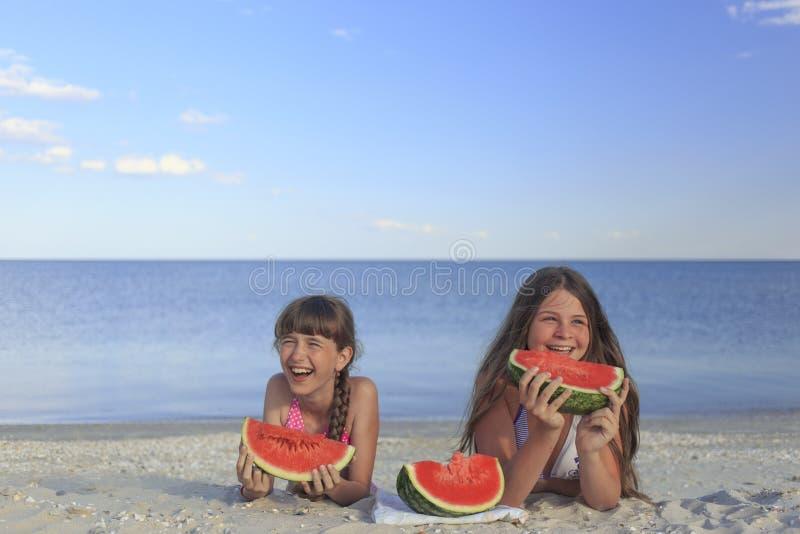 Niños felices en la playa que comen la sandía dulce fotos de archivo