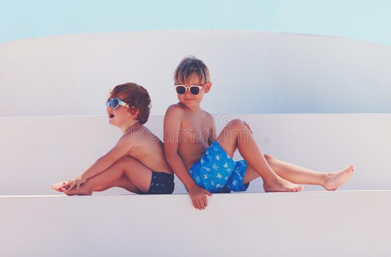 Niños felices en troncos de natación y gafas de sol el vacaciones de verano fotografía de archivo libre de regalías