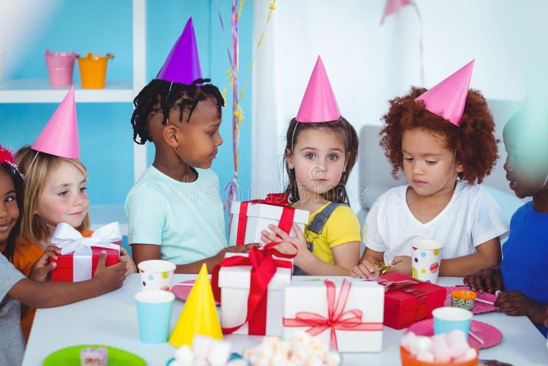 Niños felices en una fiesta de cumpleaños fotos de archivo