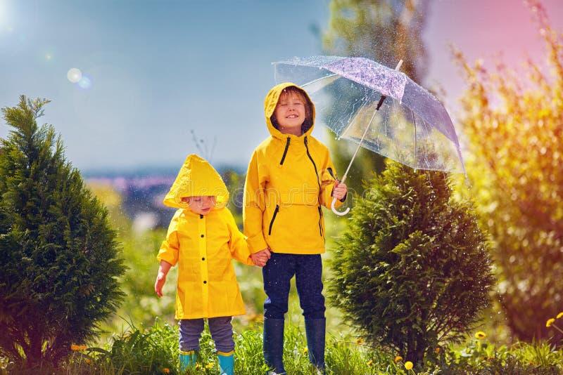 Niños felices, hermano que se divierte debajo de la lluvia soleada de la primavera foto de archivo