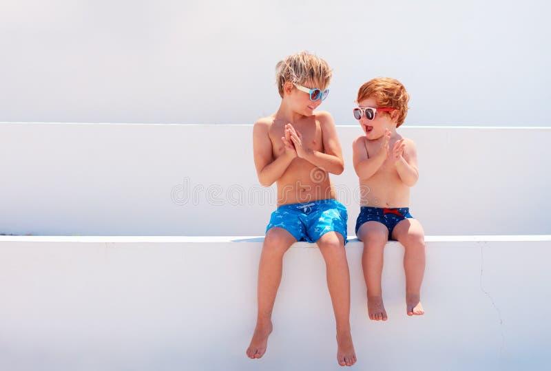 Niños felices, hermanos en los troncos del swimmimg que juegan junto imagenes de archivo