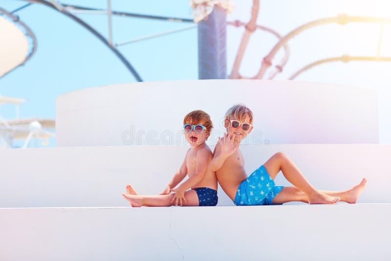 Niños felices, hermanos en los troncos del swimmimg que se relajan cerca de la piscina fotografía de archivo libre de regalías