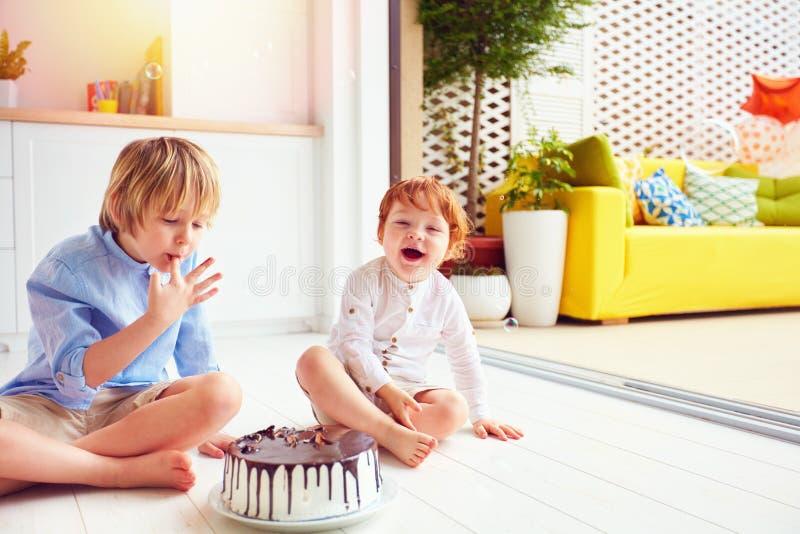 Niños felices, hermanos que prueban la torta de cumpleaños en casa fotografía de archivo libre de regalías