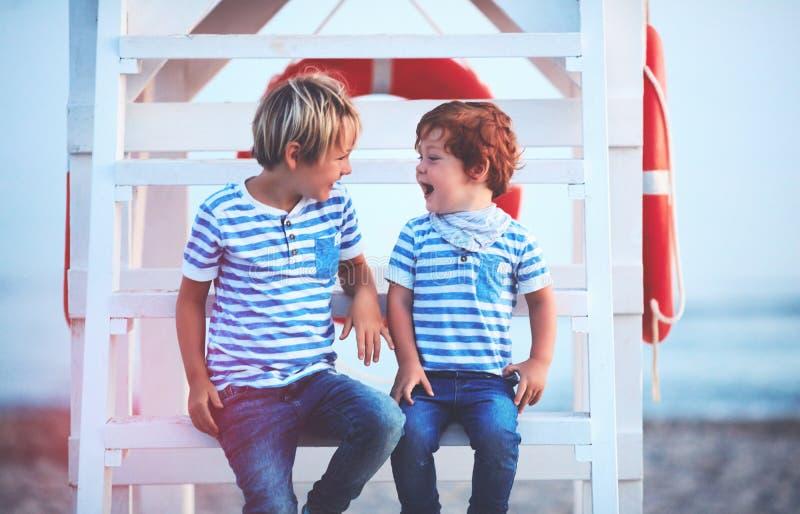 Niños felices lindos, hermanos que ríen junto, mientras que se sienta en torre del salvavidas en la playa de igualación imagenes de archivo