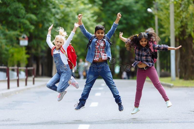 Niños felices mezclados del grupo racial que saltan en el parque cerca de escuela Concepto de la educación primaria imagen de archivo