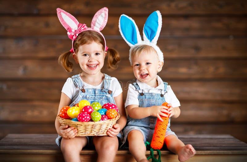 Niños felices muchacho y muchacha vestidos como conejitos de pascua con la cesta de fotografía de archivo libre de regalías