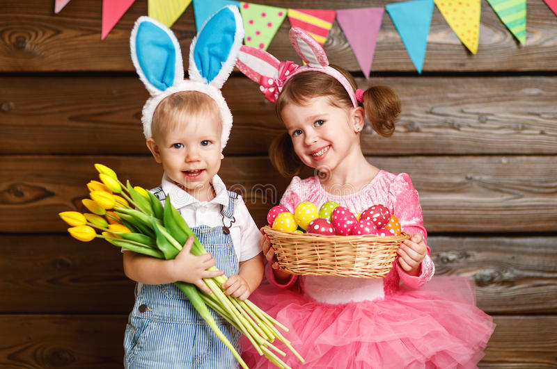 Niños felices muchacho y muchacha vestidos como conejitos de pascua con la cesta de imagen de archivo libre de regalías