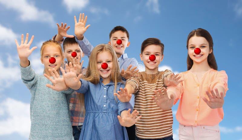Niños felices que agitan las manos en el día rojo de la nariz fotografía de archivo libre de regalías