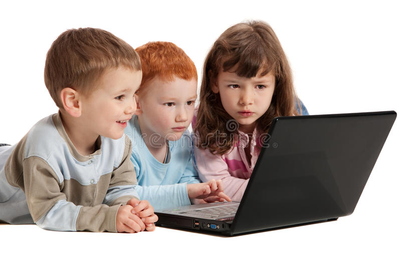Niños felices que aprenden en el ordenador portátil de los cabritos fotos de archivo