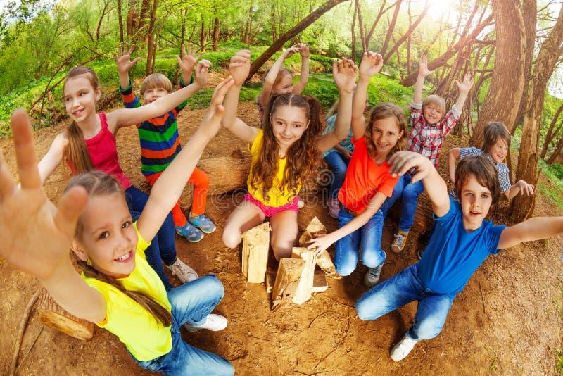 Niños felices que aumentan sus manos para arriba en el bosque foto de archivo