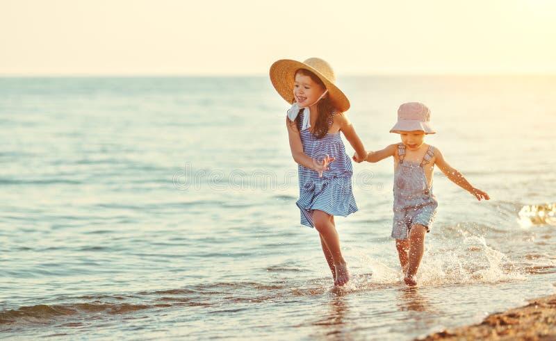 Niños felices que caminan en la playa por el mar imagen de archivo libre de regalías