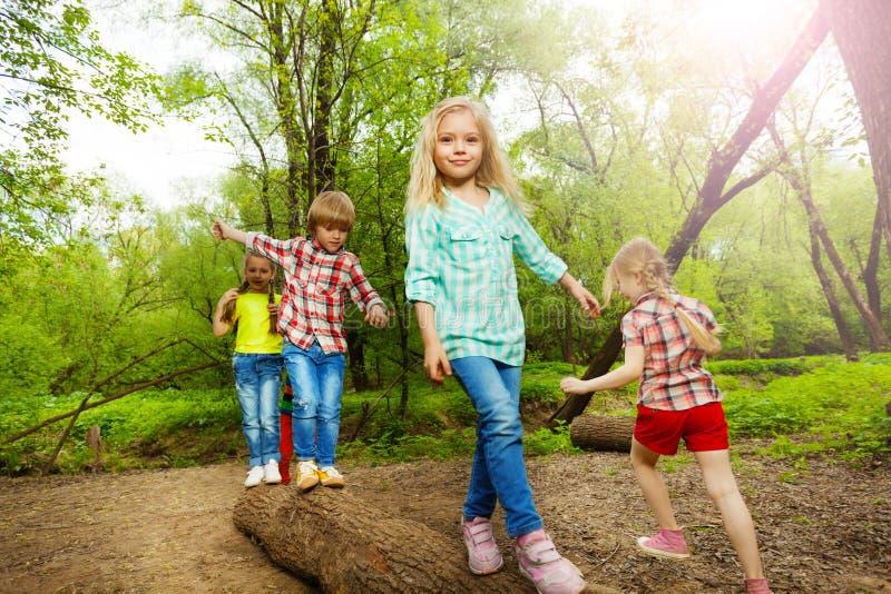 Niños felices que caminan en registro y que equilibran en bosque fotografía de archivo libre de regalías