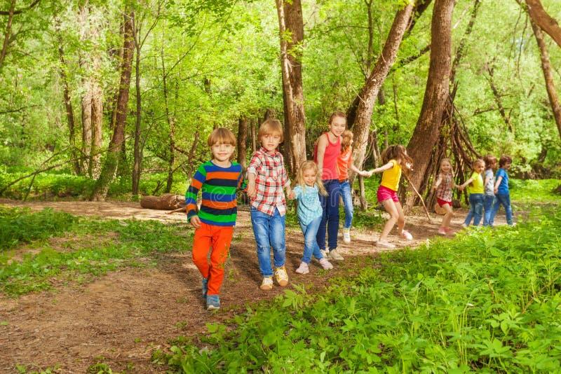 Niños felices que caminan juntas llevando a cabo las manos en parque fotos de archivo