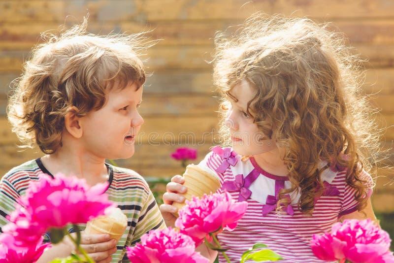 Niños felices que comen el helado en parque del verano Filtro de Instagram imagen de archivo