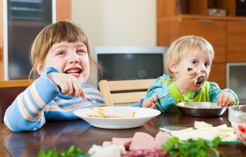 Niños felices que comen la comida imagen de archivo