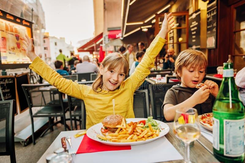 Niños felices que comen la hamburguesa con las patatas fritas y la pizza fotos de archivo libres de regalías