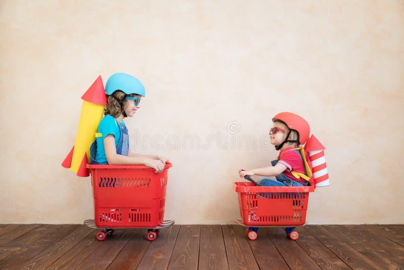 Niños felices que conducen el coche del juguete en casa imagen de archivo