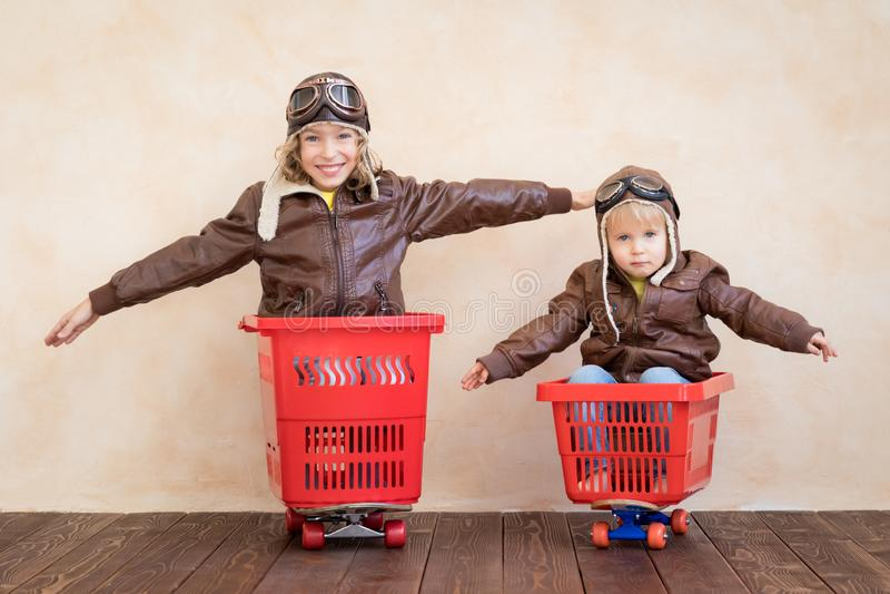 Niños felices que conducen el coche del juguete en casa imagen de archivo libre de regalías