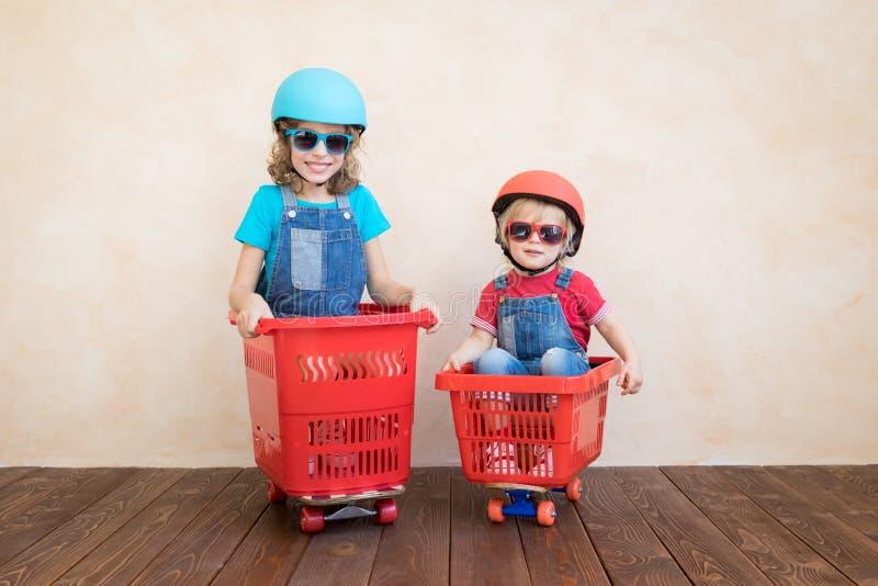 Niños felices que conducen el coche del juguete en casa imágenes de archivo libres de regalías