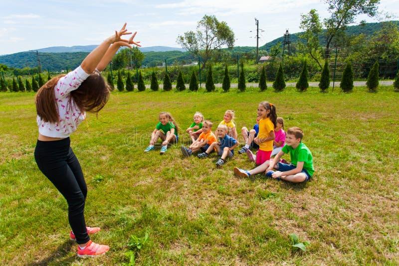 Niños felices que conjeturan durante juego de las charadas en el campamento de verano imagen de archivo libre de regalías