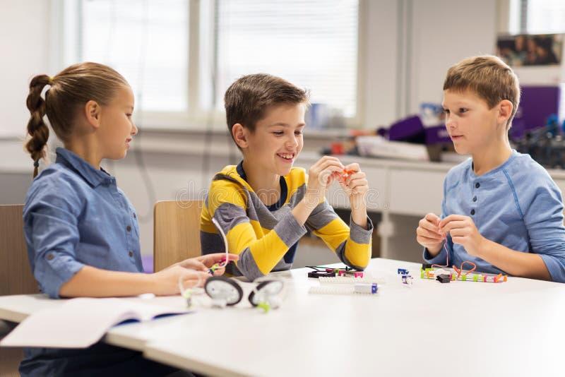 Niños felices que construyen los robots en la escuela de la robótica foto de archivo libre de regalías