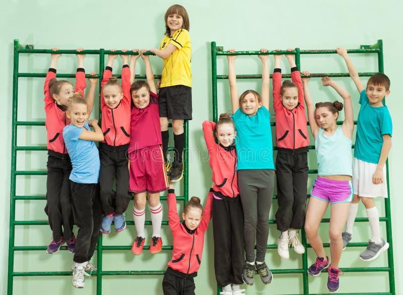 Niños felices que cuelgan en las barras de pared en gimnasio de la escuela imagen de archivo