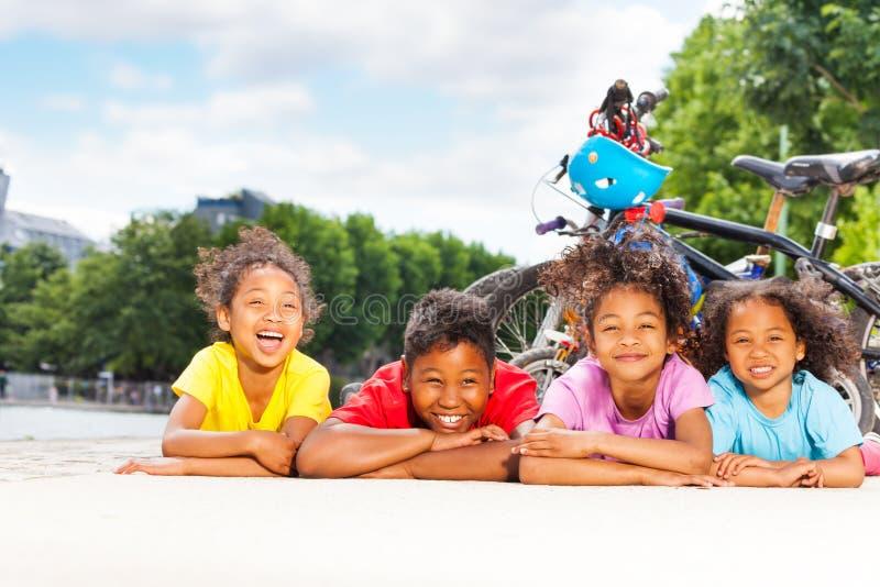 Niños felices que descansan después de completar un ciclo al aire libre imagenes de archivo