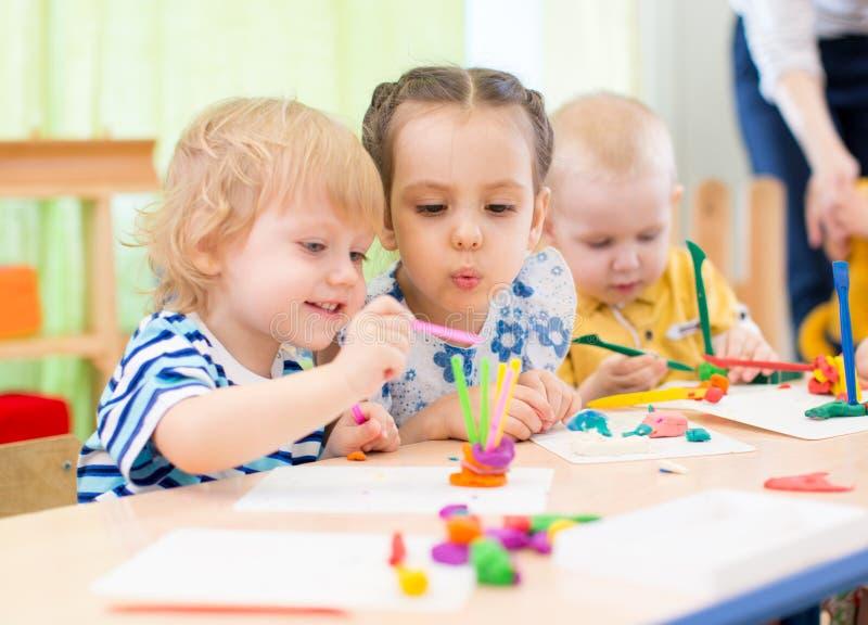 Niños felices que hacen artes y artes en centro de cuidado de día foto de archivo libre de regalías