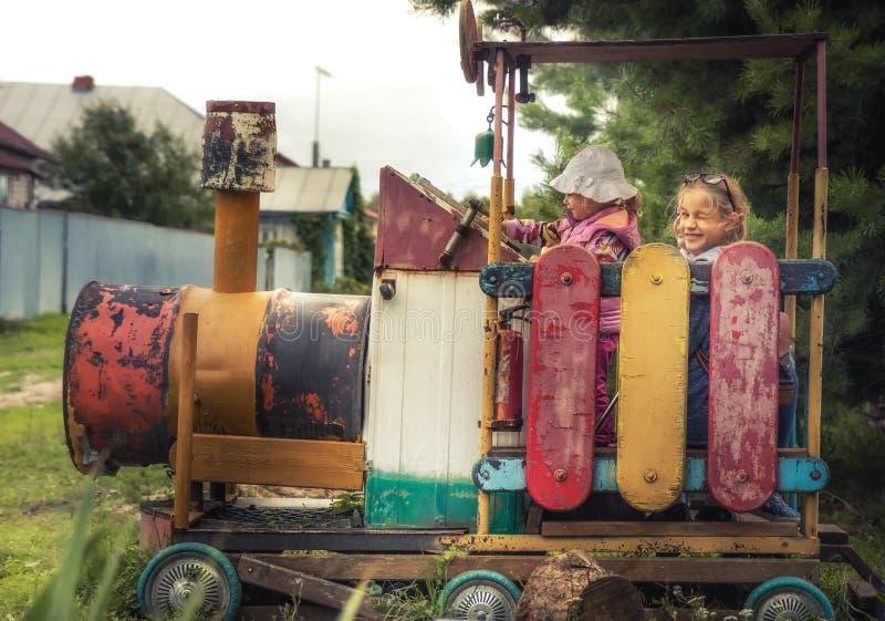 Niños felices que juegan al aire libre en el tren del vintage del patio durante vacaciones de verano en niño despreocupado feliz  imagen de archivo libre de regalías