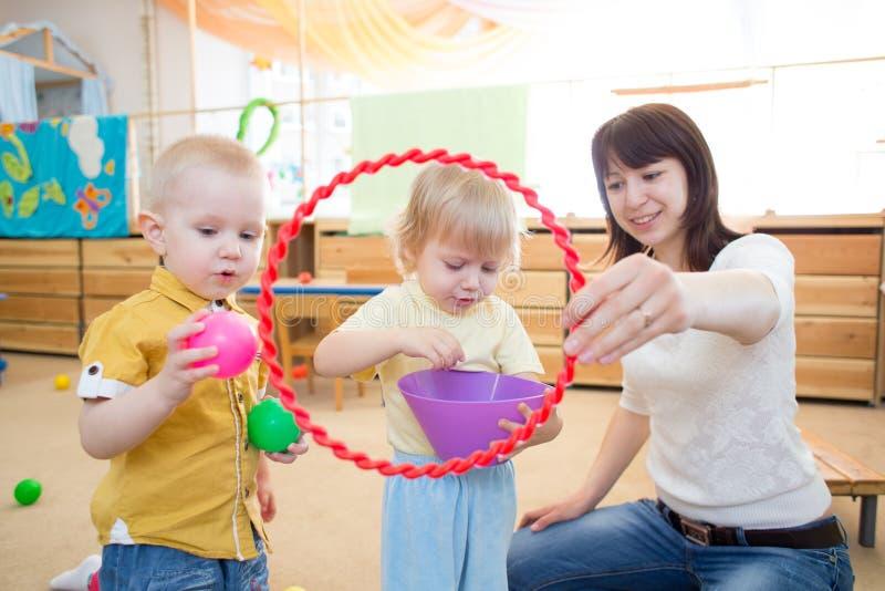Niños felices que juegan con la bola y el anillo en guardería fotografía de archivo