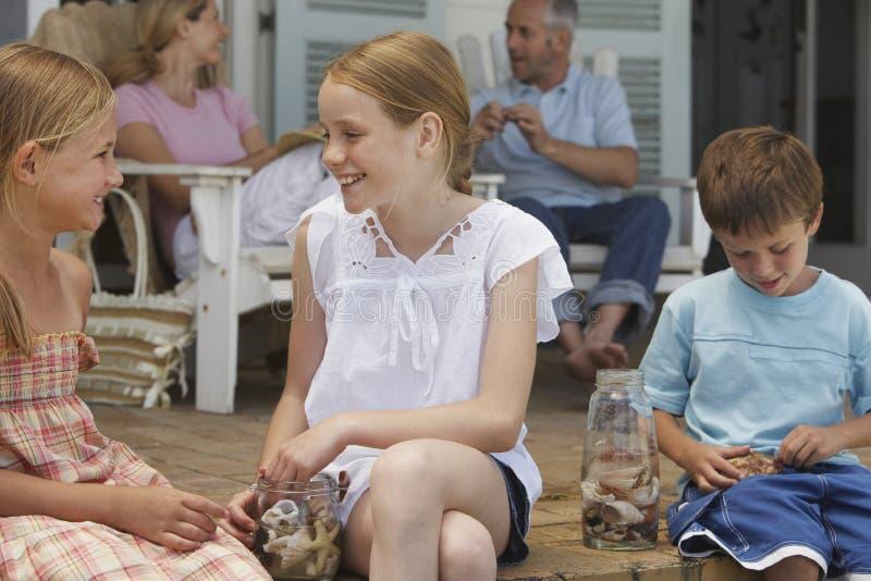 Niños felices que juegan con las conchas marinas en el pórtico foto de archivo libre de regalías