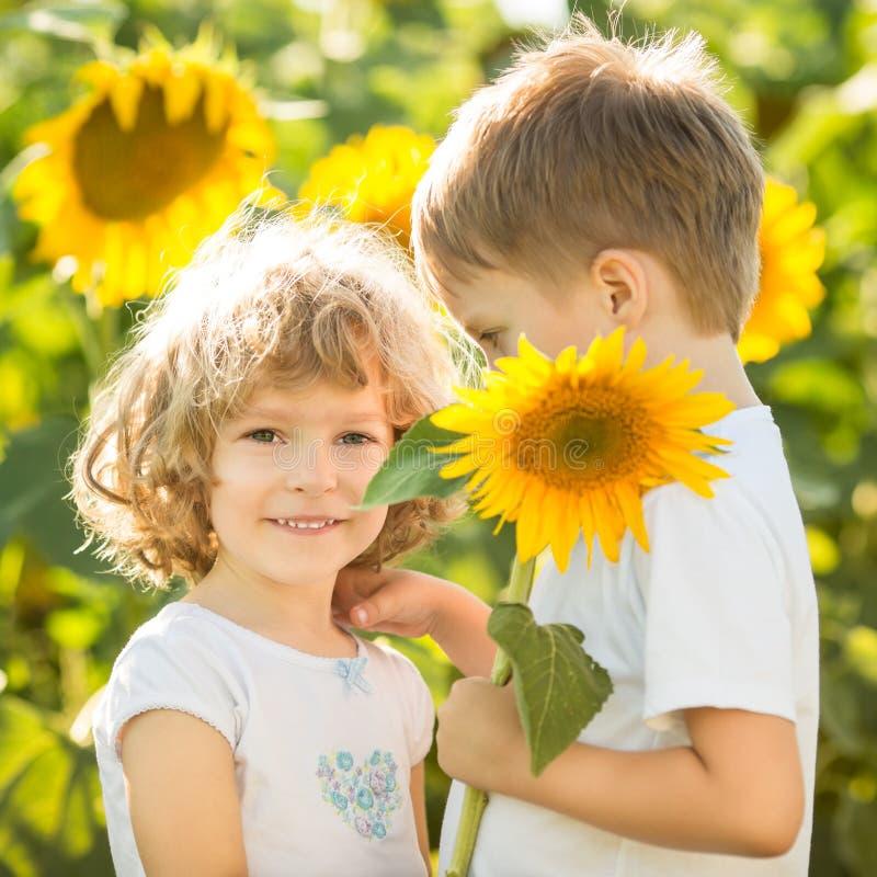 Niños felices que juegan con los girasoles imagenes de archivo