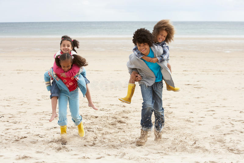 Niños felices que juegan a cuestas en la playa imagenes de archivo